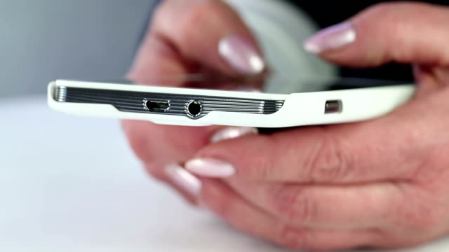Closeup of woman hands with white cell phone. Woman typing sms on her smartphone video