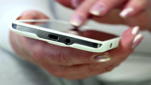 vídeos de stock e filmes b-roll de grande plano de mulher mãos com smartphone branco - contacts