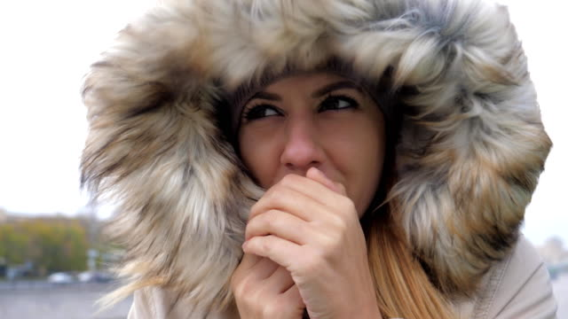 vídeos y material grabado en eventos de stock de primer plano de mujer en una chaqueta con capucha que cerró el fuerte viento frío - frío