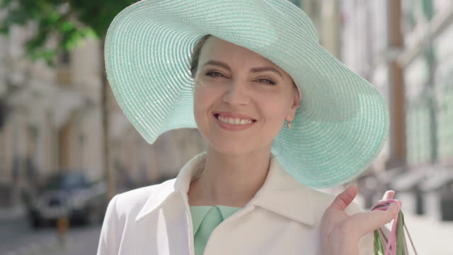 close-up of woman in elegant turquoise hat raising shopping bags on shoulder and turning to camera. portrait of happy smiling caucasian lady posing on sunny city street with purchases. - staw człowieka filmów i materiałów b-roll
