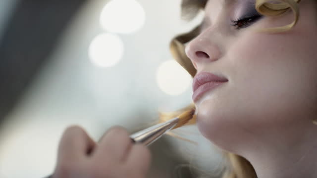 Nahaufnahme der Frau, die ihr Gesicht mit Pinsel Haare und Make-up auflegen – Video