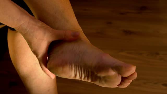 Closeup of woman massaging ankle and stretching foot suffering from pain video