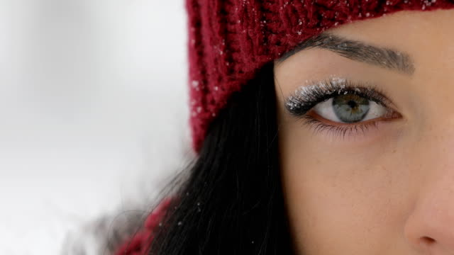 Close-up of woman open her eyes with snow on big eyelashes video