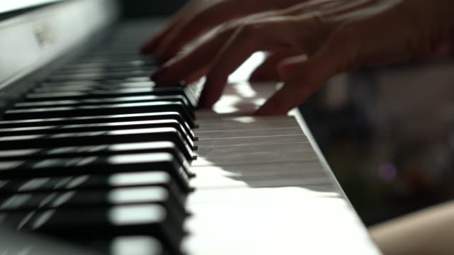 vídeos de stock e filmes b-roll de close-up of woman playing a piano - instrumental
