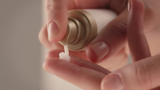 nahaufnahme der frau drückt sahne auf die finger - kosmetik stock-videos und b-roll-filmmaterial