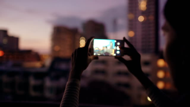 Closeup of woman taking photo of cityscape view with smartphone in bar rooftop terrace at night