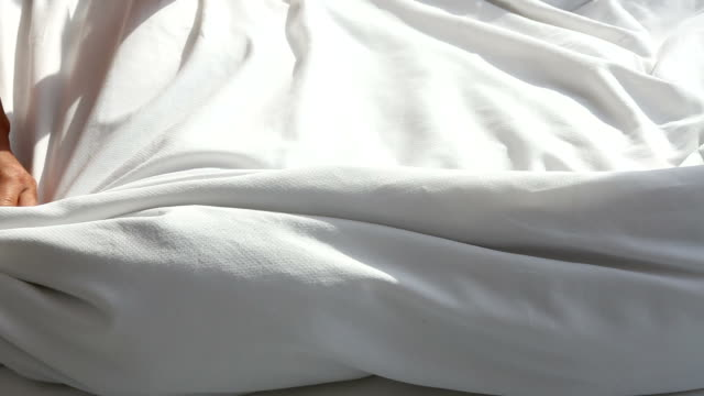 closeup of woman throwing white blanket on bed
