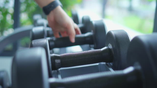 Close-up of woman try dumbbell,Slow motion