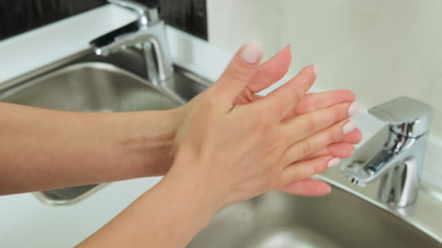 Close-up of woman using hand sanitizer gel on the background of the sink Close-up of woman using hand sanitizer gel to prevent spreading virus on the background of the sink in the clinic. Hygiene, treatment, medicine concept. household fixture stock videos & royalty-free footage