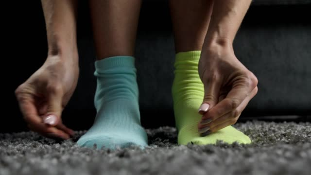close-up of woman wearing mismatched socks - calzino video stock e b–roll
