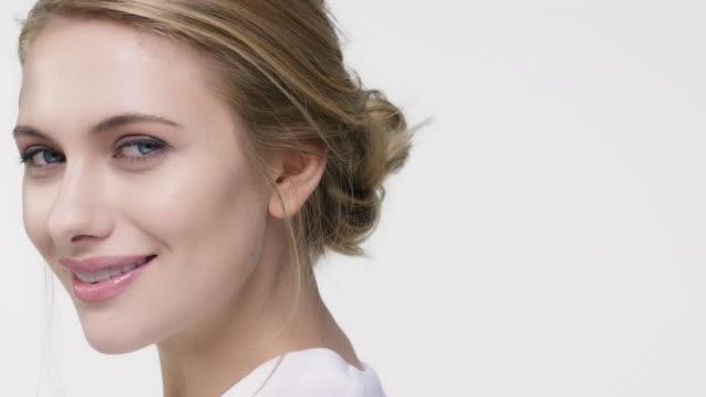 白い背景に、ウインク女性のクローズ アップ - スキンケア点の映像素材/bロール