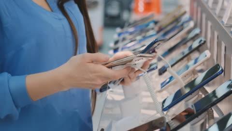 vídeos de stock, filmes e b-roll de close up da mão da mulher que escolhe comprando um telefone esperto novo perto de um indicador da loja em uma loja da eletrônica - smartphone