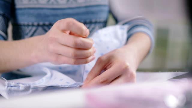 närbild av kvinnas hand sy quiltning - på gränsen bildbanksvideor och videomaterial från bakom kulisserna