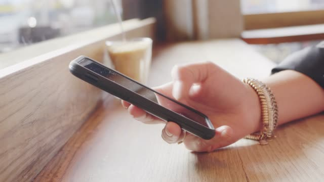 Closeup Of Woman's Hand Using Smart Phone In Coffee Shop Closeup of woman's hand using smart phone in coffee shop. Female is tapping and scrolling screen of mobile phone at table. She is wearing bracelet in cafe. 4K Resolution. tapping stock videos & royalty-free footage