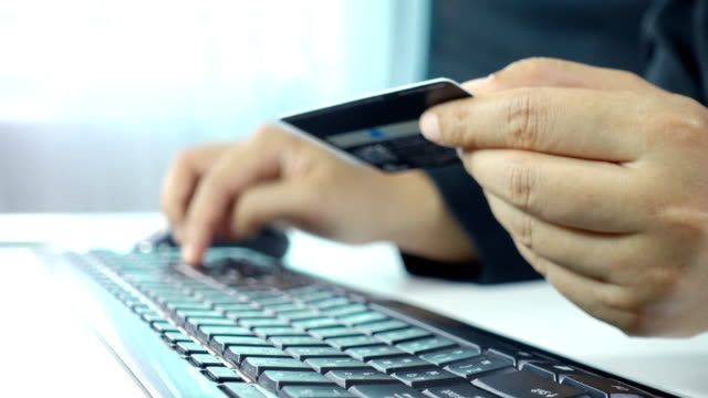 Closeup of woman's hands holding a credit card and using computer for online shopping in workspace Video record with compact camera in studio shot. credit card purchase stock videos & royalty-free footage