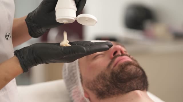 a closeup of woman's hands in black gloves squeezing cream and applying it on man's forehead, cheekbones, neck. the man is lying on the couch in a beauty salon and the woman is standing at his head - kosmetyczka praca w salonie piękności filmów i materiałów b-roll