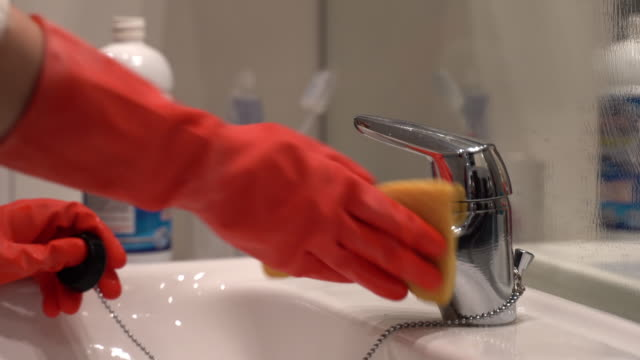 close-up of woman's hands in protective orange gloves washing stainless faucet and white sink in the bathroom. housewife using yellow cleaning sponge and bleach or gel disinfectant. cleaning bathroom - bleach stock videos & royalty-free footage