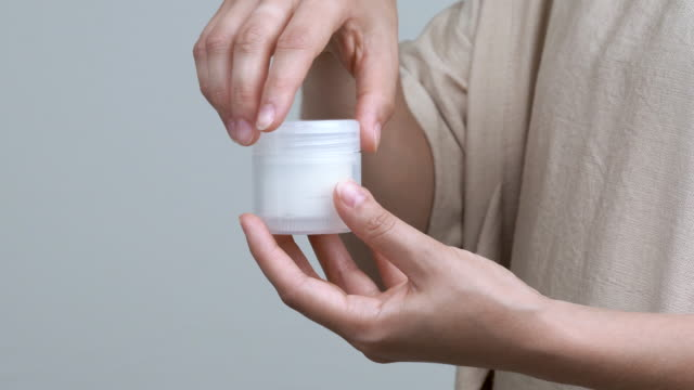 Close-up of woman's hands opening a jar with cream on the white background. The container is held vertically. Close-up of woman's hands opening a jar with cream on the white background. The container is held vertically. serum sample stock videos & royalty-free footage