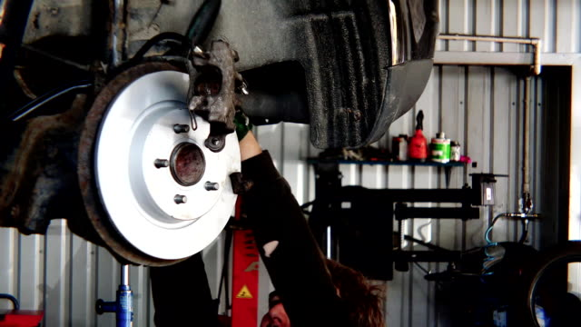 closeup of worker man mounting new brake disk on old car lifted in repair shop. video