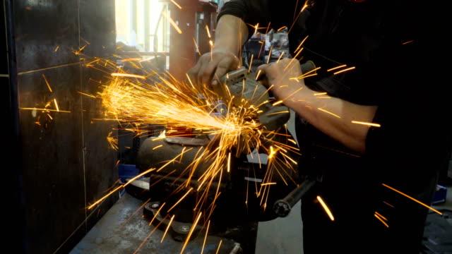 nahaufnahme des arbeiters mit einem schleifer schneidet metall in einer werkstatt - grind stock-videos und b-roll-filmmaterial