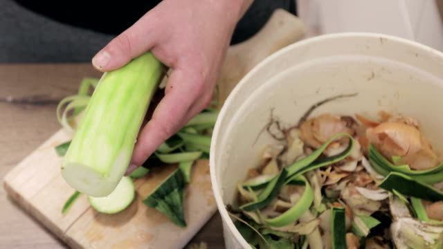 Close-up of Young Adult Man Peeling Zucchini and Putting Peelings Into Organic Waste Bucket video