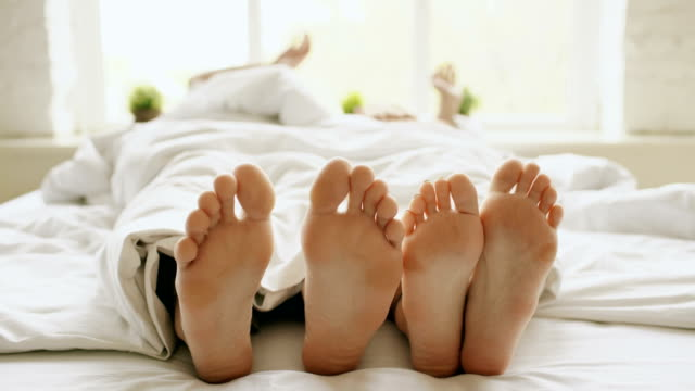 Closeup of young beautiful and loving couple play and dance their feet under blanket while wake up in bed in morning