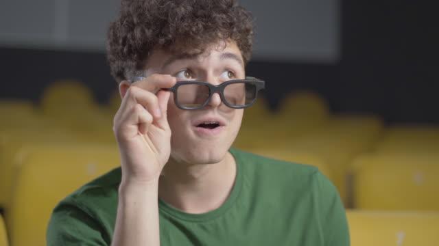 vidéos et rushes de plan rapproché du jeune homme gai regardant le film 3d dans le cinéma. verticale du visiteur caucasien absorbé joyeux avec les cheveux bouclés et les yeux bruns mettant vers le bas des lunettes 3d et souriant. - abaisser
