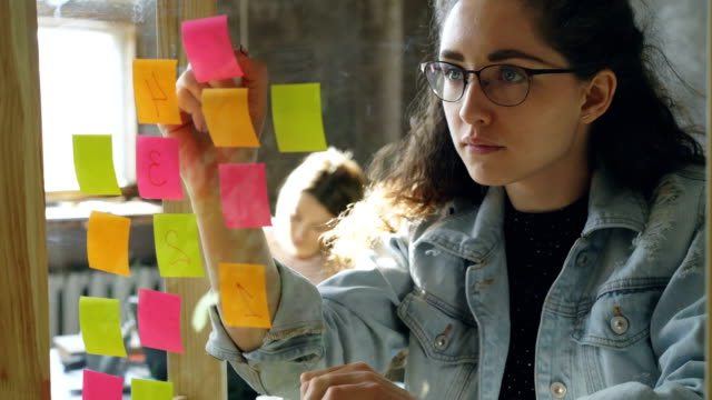 close-up of young creative entrepreneur numbering coloured stickers on glassboard while working together with female colleague in modern office - post it video stock e b–roll