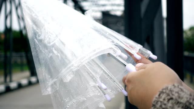 vídeos de stock e filmes b-roll de close-up of young female hand opens umbrella in raining day, slow motion shot - guarda chuva