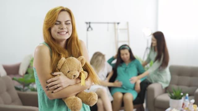 vidéos et rushes de plan rapproché de jeune fille avec le long cheveu rouge retenant l'ours de nounours et souriant doucement à l'appareil-photo - fête de naissance