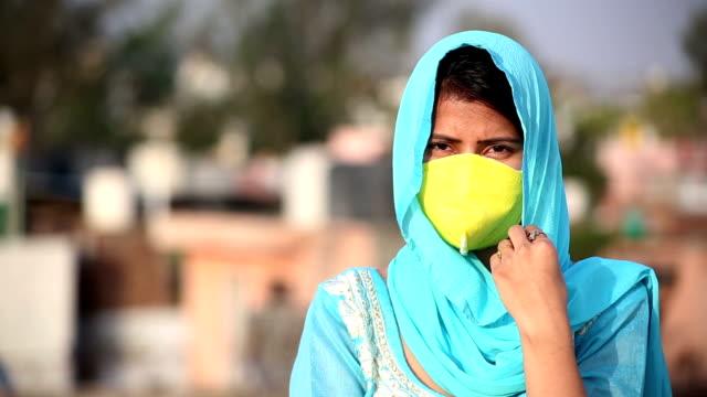 Close-Up de jovens mulheres indianas cobrindo seu rosto com máscara de poluição para proteção do COVID-19 - vídeo