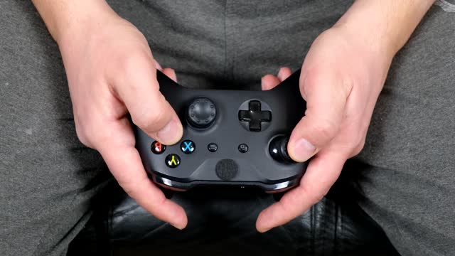 Closeup of young man hands playing video games on Gamepad. Closeup.