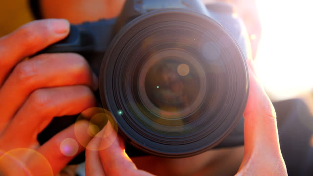 close-up of young man photographing with camera at sunset - obiettivo video stock e b–roll