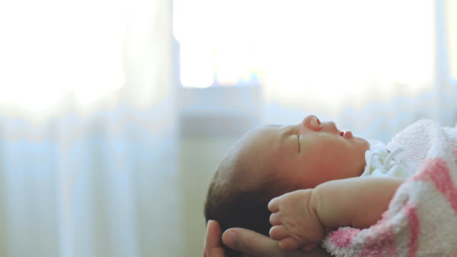 Close-up Of Young Mother Holding Her Newborn Baby