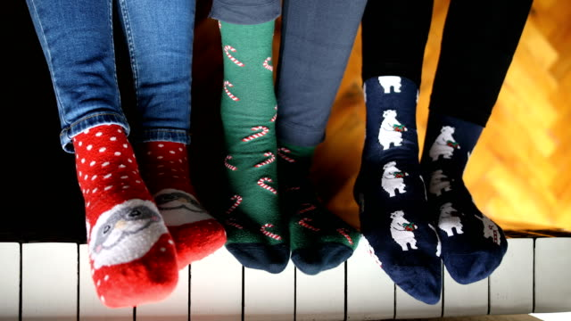 close-up of young people dressed in christmas socks sitting near the radiator - носок стоковые видео и кадры b-roll