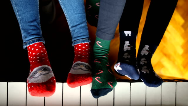 vídeos y material grabado en eventos de stock de primer plano de los jóvenes vestidos con calcetines de navidad sentados cerca del radiador - social media
