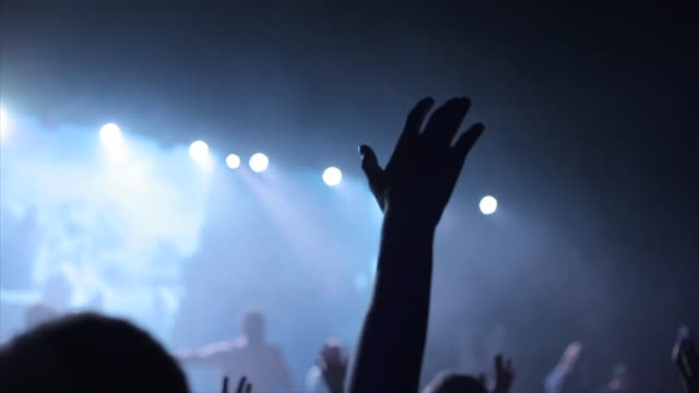 A close-up of young people raising up hands at a concert. They sing in front of the blurred stage