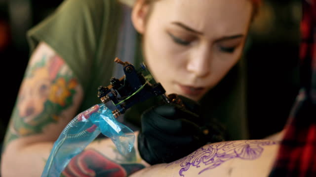 closeup of young red haired tattoo artist woman tattooing picture on leg of client over sketch in studio indoors - tatuaggio video stock e b–roll