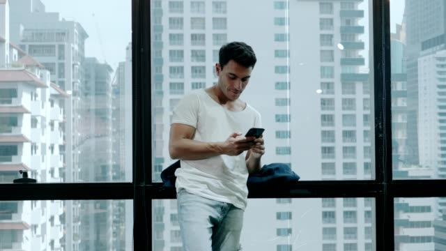 Closeup of Young smiling man using smartphone for surfing social media video