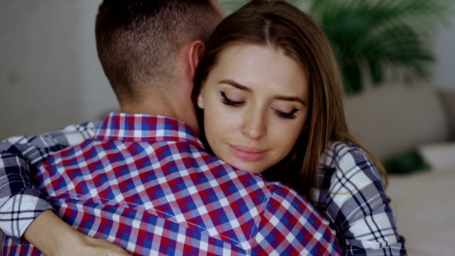 closeup of young upset couple embrace each other after quarrel. woman looking wistful and sad hug her boyfrined at home - chiedere scusa video stock e b–roll