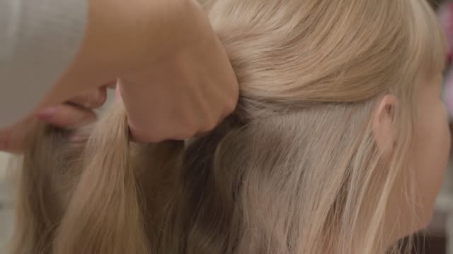 Close-up of young woman braiding a braid of her blond daughter