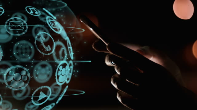 Closeup of young woman hands using smartphone with digital hologram projection of sphere with icons