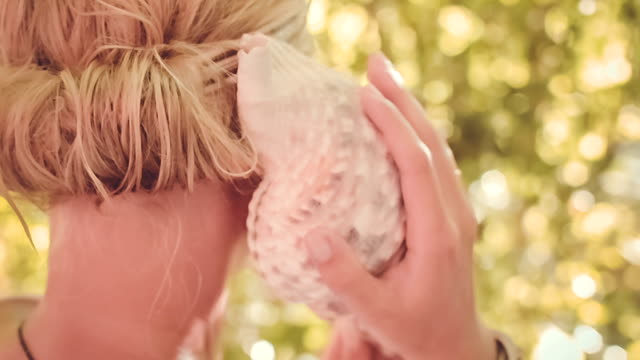 Close-up of Young woman is listening to sea shell Close-up of Young woman is listening to sea shell, plant bokeh on background. Nack kshort animal shell stock videos & royalty-free footage