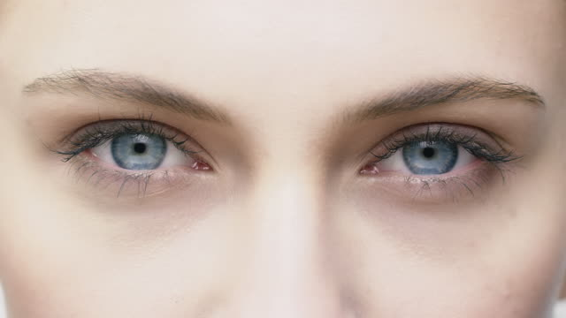 Close-up of young woman opening her blue eyes