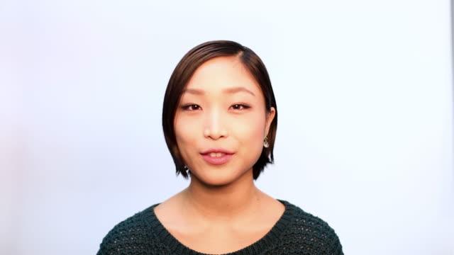 話し、笑顔の若い女性のクローズアップ - スタジオ 日本人点の映像素材/bロール