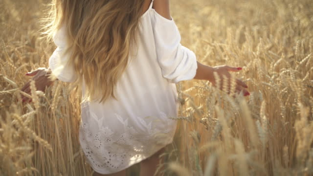 A close-up of young woman walking and touching ears of wheat in the field on sunset. Natural beauty concept