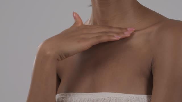 vidéos et rushes de plan rapproché de la jeune femme avec la peau saine lisse touchant doucement son décolleté avec des doigts. isolé, sur le fond blanc - peau humaine