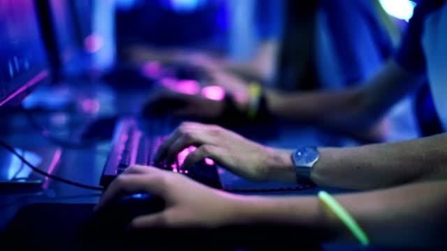 close-up auf zeile der gamer hände auf eine keyboard.jpgs aktiv drücken von tasten, mmo spiele online zu spielen. hintergrund ist mit neonröhren beleuchtet. - computerspieler stock-videos und b-roll-filmmaterial
