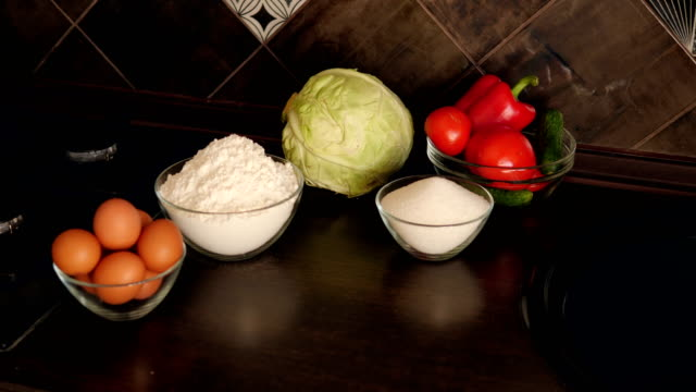 Close-up on table in the kitchen are plates of eggs, flour, sugar and vegetables