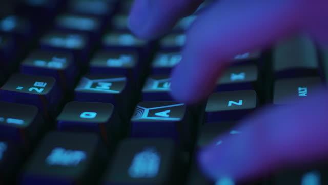 close-up auf den fingern drücken von tasten auf der stilvollen neon beleuchtete tastatur. - zahlentastatur stock-videos und b-roll-filmmaterial